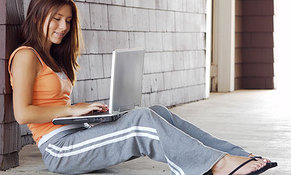 Woman happily using laptop after screen repair.